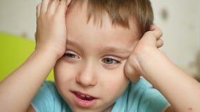 有喜悦和微笑的一个孩子看照相机,握他的在他的头后的手,关闭他的耳朵,特写镜头 股票视频