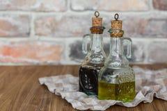 有喷口的油和香醋玻璃瓶在土气砖墙背景的一块餐巾与拷贝空间 免版税库存照片