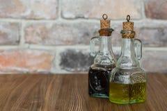 有喷口的油和香醋玻璃瓶在与拷贝空间的土气砖墙背景 免版税库存图片