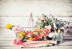 有喷壶、篮子和花的园艺工具在木背景的从事园艺的桌上 图库摄影