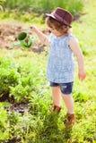 有喷壶的小女孩在庭院里 图库摄影