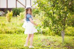 有喷壶的小女孩在庭院里 免版税库存照片