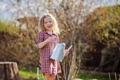 有喷壶的愉快的儿童女孩在春天庭院里 免版税库存照片