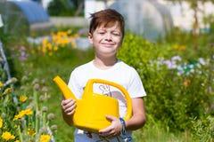 有喷壶的逗人喜爱的男孩在庭院里 图库摄影