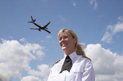 有喷气式客机的妇女飞行员在天空 免版税图库摄影