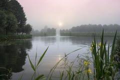 有喷泉的一个池塘在日出 库存图片