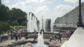 有喷泉的城市公园 人们放松并且走与孩子 在夏时 不在焦点是故意的 股票录像