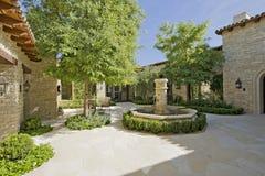 有喷泉的庭院和树在一个晴天 库存照片