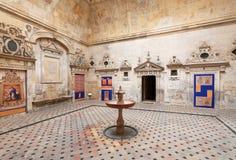 有喷泉的新生庭院在有葡萄酒装饰的16世纪塞维利亚大教堂里面 免版税库存照片