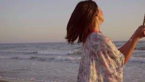有喷泉蜡烛的深色的妇女在海滩 影视素材