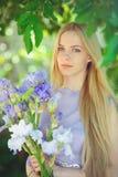 有嗅到蓝色紫色虹膜的金发和自然构成的可爱的女孩在背景开花户外,招标 免版税库存照片