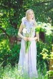 有嗅到蓝色紫色虹膜的金发和自然构成的可爱的女孩在背景开花户外,招标 免版税图库摄影