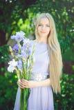 有嗅到蓝色紫色虹膜的金发和自然构成的可爱的女孩在背景开花户外,招标 库存图片