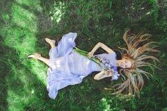 有嗅到蓝色紫色虹膜的金发和自然构成的可爱的女孩开花说谎在草户外, tendern 库存图片