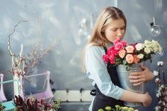 有嗅到长的公平的头发的女孩拥抱和白色和桃红色玫瑰 免版税图库摄影
