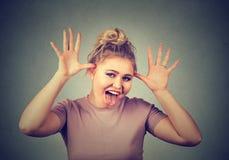 有嘲笑某人的滑稽的面孔的妇女取笑某事用一个残暴的方式 免版税图库摄影