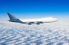 有四个引擎的飞机,没有舷窗的卡车在云彩飞行旅途太阳高度上的天空 库存图片