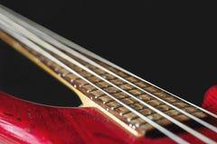 有四串的红色电低音吉他在黑暗的背景 图库摄影