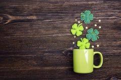 有四叶三叶草的绿色杯子在木背景 复制空间 免版税库存照片