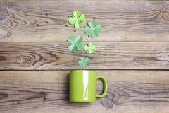 有四叶三叶草的绿色杯子在木背景 免版税图库摄影