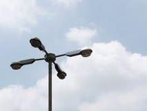 有四条胳膊的街道路灯柱在多云蓝天 免版税库存图片
