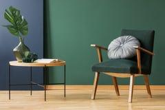 有回合的,在木咖啡桌旁边的银色枕头减速火箭的苔绿色扶手椅子与在玻璃花瓶,在空的墙壁上的拷贝空间的叶子 库存照片