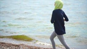 有回教的女孩在Pebble海滩的凹凸部训练 股票视频
