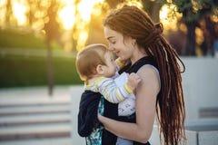 有因此背包的走在晴朗的夏日的小儿子的年轻愉快的母亲 母性喜悦的概念  库存照片