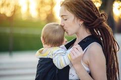 有因此背包的走在晴朗的夏日的小儿子的年轻愉快的母亲 母性喜悦的概念  库存图片