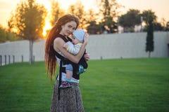 有因此背包的走在晴朗的夏日的小儿子的年轻现代母亲 母性喜悦的概念  免版税库存照片
