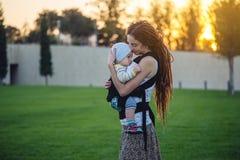 有因此背包的走在晴朗的夏日的小儿子的年轻现代母亲 母性喜悦的概念  图库摄影