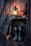 有园艺工具和油灯的一个老土气棚子 免版税库存照片