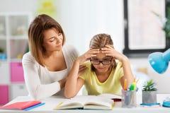 有困难的家庭作业的母亲帮助的女儿 库存图片