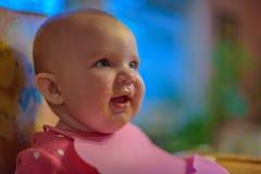 有围嘴的愉快的婴孩在葡萄酒hight椅子 免版税库存图片