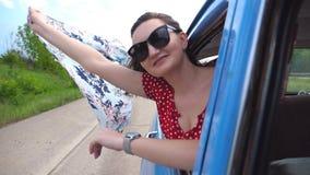 有围巾的少女在她的倾斜在葡萄酒汽车外面窗口和享受乘驾的手上 可爱的纵向妇女 股票录像