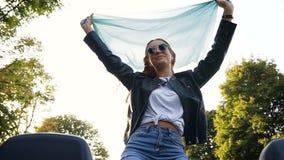 有围巾的愉快的年轻女人获得乐趣在汽车 股票视频