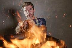 有围裙的年轻滑稽和杂乱家庭厨师人在拿着在火的震动平底锅烧在厨房灾害和国内厨师的食物 库存图片