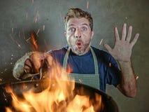 有围裙的年轻滑稽和杂乱家庭厨师人在拿着在火的震动平底锅烧在厨房灾害和国内厨师的食物 免版税库存图片