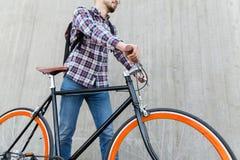 有固定的齿轮自行车和背包的行家人 库存照片