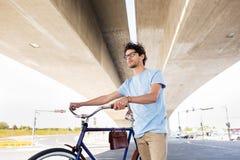 有固定的齿轮自行车的行家人在桥梁下 免版税库存图片