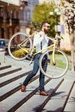 有固定自行车的有胡子的人 看起来观点的确信的年轻有胡子的人运载他的在肩膀的自行车和去,当走时 图库摄影