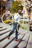 有固定自行车的有胡子的人 看起来观点的确信的年轻有胡子的人运载他的在肩膀的自行车和去,当走时 免版税库存图片
