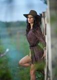 有国家神色的美丽的深色的女孩,户外在木篱芭,土气样式附近射击了 可爱的牛仔帽妇女 免版税库存照片