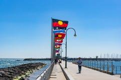 有国旗行的St Kilda码头与澳大利亚人Aborig的 图库摄影