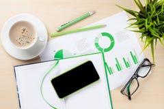 有图、咖啡、植物和电话的办公桌 免版税库存图片