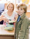 有图书管理员扫描书的男孩在图书馆 图库摄影