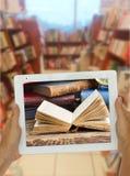 有图书馆shelfs的片剂在背景中 库存图片