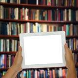 有图书馆shelfs的空的片剂在背景中 库存图片