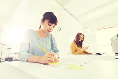 有图纸文字的建筑师妇女在办公室 库存图片