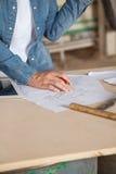 有图纸的女性木匠在表上 免版税库存照片